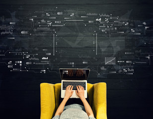 Wall Mural - Technology screen with person using a laptop in a chair