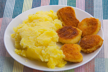 Boiled mashed potatoes on a plate with chicken nuggets on table