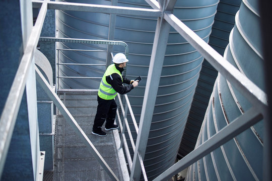 Factory silos worker standing on metal platform between industrial storage tanks and looking at tablet about food production.