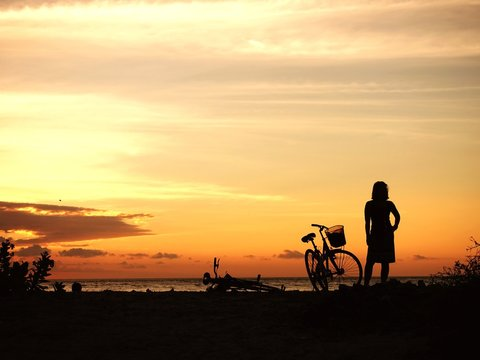 Rear View Of Silhouette Woman Standing By Bicycle At Beach During Sunset