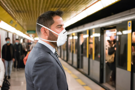 Masked businessman entering the subway, coronavirus urban transportation and safety concept