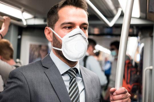 Masked businessman riding the subway, coronavirus urban transportation and safety concept
