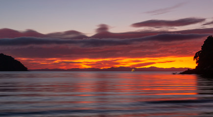 Dramatic sunrise at sea. Abel Tasman National Park, New Zealand