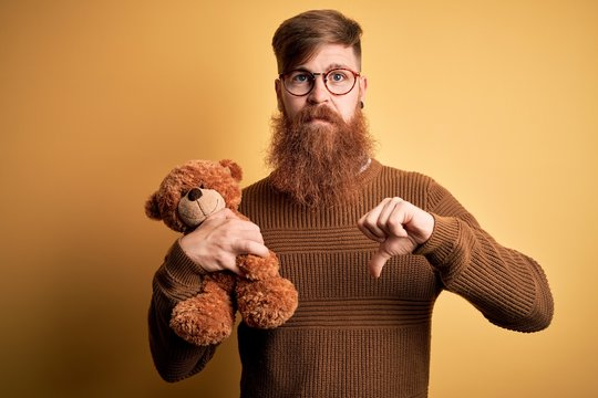 Redhead Irish man with beard hugging teddy bear stuffed animal over yellow isolated background with angry face, negative sign showing dislike with thumbs down, rejection concept