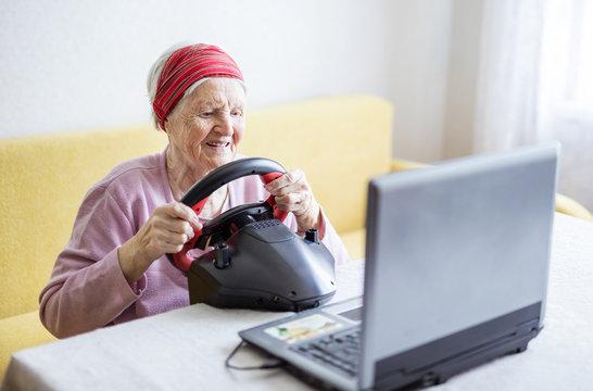 Senior woman enjoying car racing video game on laptop