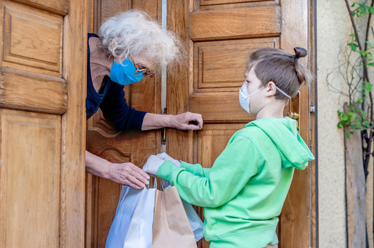 Teen grandson gives grandmother purchases from the store through a door sill. Help for single people. Food for the elderly. Family support, caring . Elderly quarantined, isolated. Coronavirus covid-19