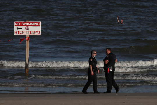 Man signals towards police after running into closed beach during coronavirus disease (COVID -19) pandemic in Galveston, Texas