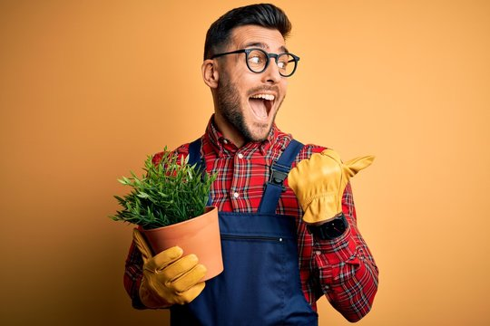 Young gardener man wearing working apron gardening plat for hobby over yellow background pointing and showing with thumb up to the side with happy face smiling