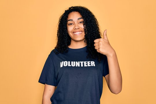 Young african american curly woman doing volunteering wearing volunteer t-shirt happy with big smile doing ok sign, thumb up with fingers, excellent sign