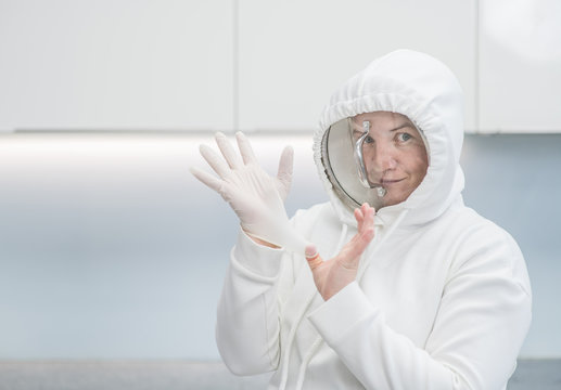 Woman fooling around at home during coronavirus quarantine, dressed up in a funny protective suit with a pan cover and latex gloves