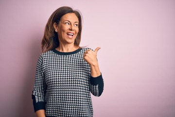 Wall Mural - Middle age beautiful woman wearing casual sweater standing over isolated pink background smiling with happy face looking and pointing to the side with thumb up.
