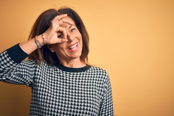 Wall Mural - Middle age beautiful woman wearing casual sweater over isolated yellow background doing ok gesture with hand smiling, eye looking through fingers with happy face.