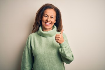 Wall Mural - Middle age beautiful woman wearing casual turtleneck sweater over isolated white background doing happy thumbs up gesture with hand. Approving expression looking at the camera showing success.