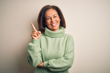 Wall Mural - Middle age beautiful woman wearing casual turtleneck sweater over isolated white background with a big smile on face, pointing with hand and finger to the side looking at the camera.