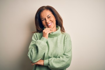 Wall Mural - Middle age beautiful woman wearing casual turtleneck sweater over isolated white background looking confident at the camera with smile with crossed arms and hand raised on chin. Thinking positive.