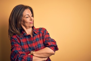Wall Mural - Middle age beautiful woman wearing casual shirt standing over isolated yellow background looking to the side with arms crossed convinced and confident