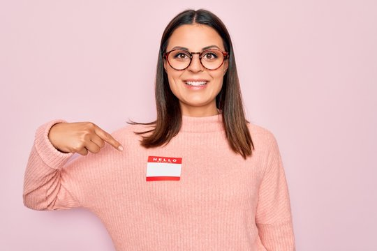 Young beautiful brunette woman wearing sticker with hello my name is message Smiling happy pointing with hand and finger