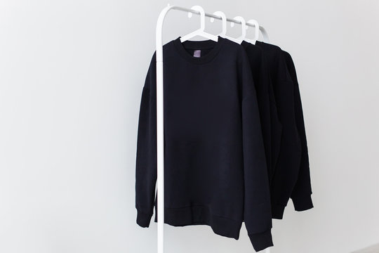 Sweatshirts and hoodies hanging on hangers in the store. Street fashion, unisex and youth wears.