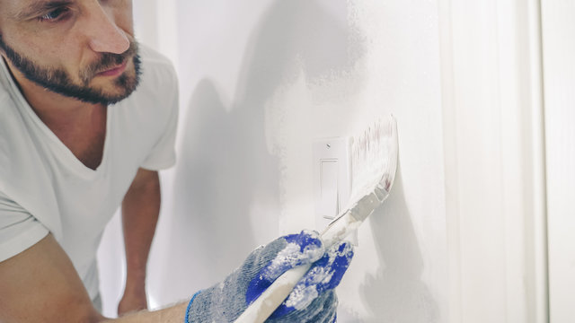 Close up of painter hands with gloves painting the wall edge with brush.