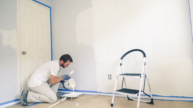 Professional interior construction worker pouring white color paint to tray.