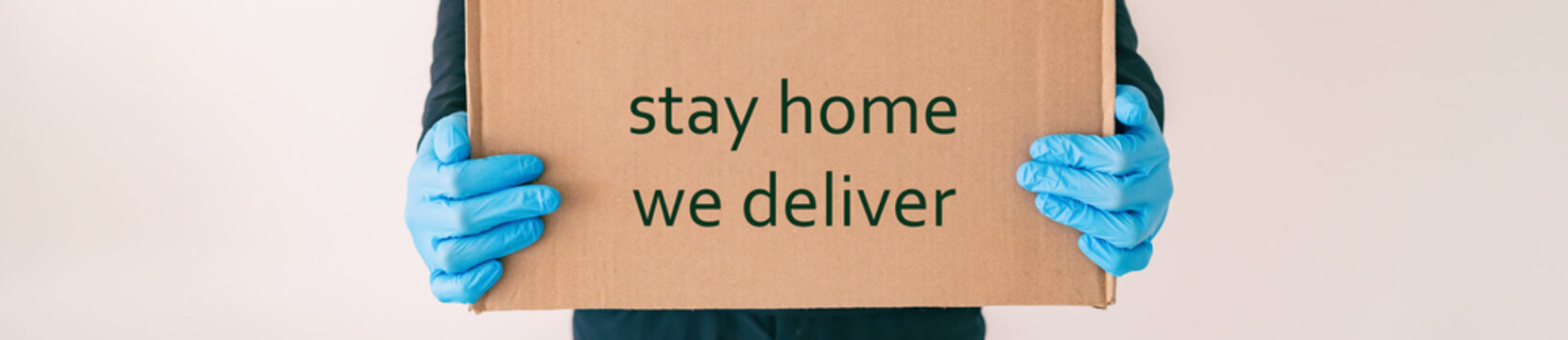 Home delivery with quote STAY HOME WE DELIVER on cardboard box banner. Food grocery delivered with gloves for COVID-19 quarantine from coronavirus social distancing. man giving purchase.