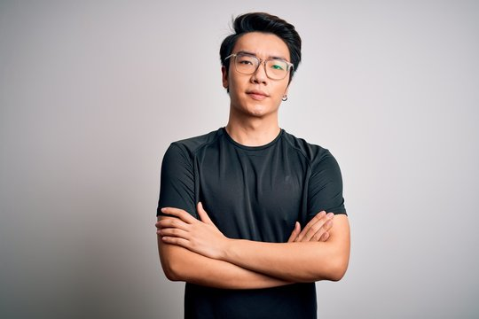 Young handsome chinese man wearing black t-shirt and glasses over white background skeptic and nervous, disapproving expression on face with crossed arms. Negative person.