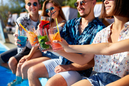 Close view. Friends clinking glasses with fresh colorful cocktails sitting by swimming pool on sunny summer day. People toast drinking beverages at luxury villa poolside party on tropical vacation.