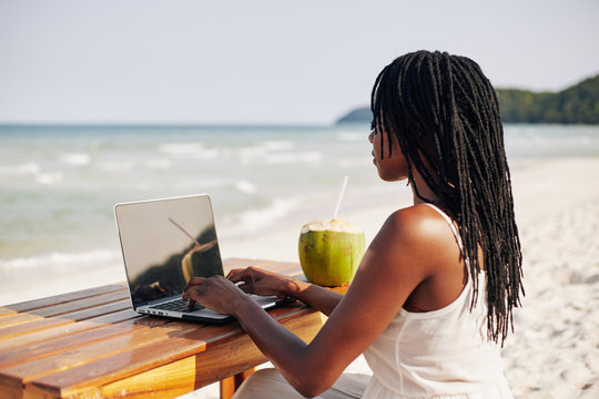 Black young woman with dreadlocks working on computer when sitting at desk on the beach