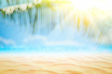 Wall Mural - Blur beautiful nature green palm leaf on tropical beach with bokeh sun light wave abstract background.