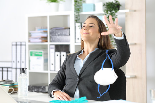 Executive breathing fresh air throwing protective mask