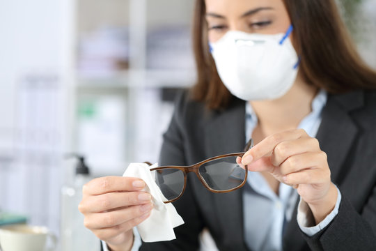 Executive wearing mask disinfecting glasses with sanitizer