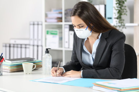 Executive with mask signing contract at office
