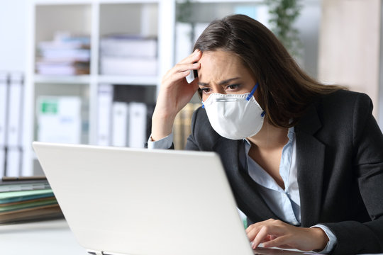 Worried executive with mask reading bad news on laptop
