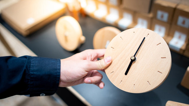 Male hand customer choosing circle wooden clock in art and craft decor shop. Buying instrument of time for home decoration. Time concept