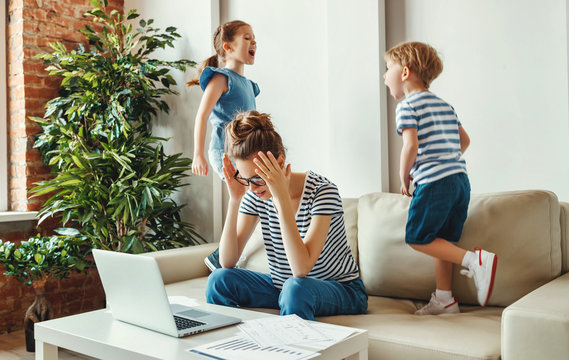 Stressed woman with kids working from home