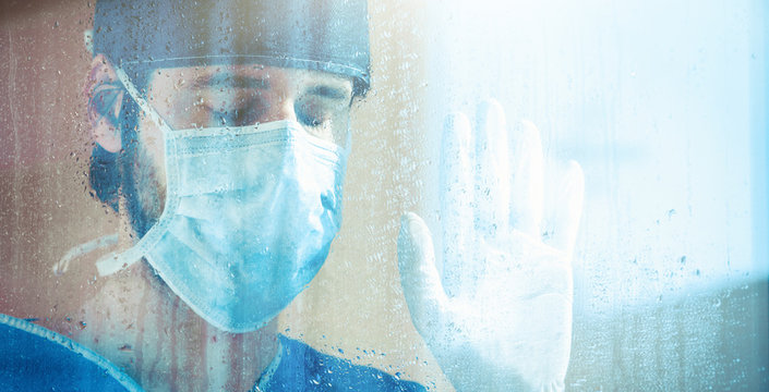 Medico o infermiere stanco guarda fuori dalla finestra dell'ospedale, bagnata dalla pioggia.