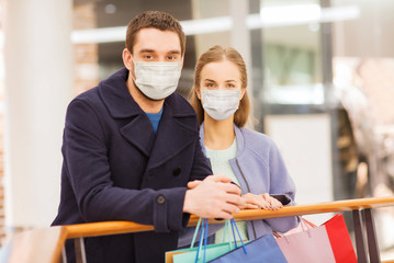 sale, consumerism and pandemic concept - happy young couple wearing face protective medical mask...