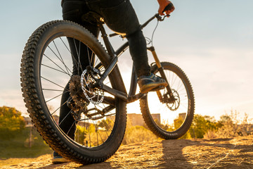 Man on mountain bike. Bicycle wheels close up image on sunset. Low angle view of cyclist riding mountain bike. Foot on pedal. Fototapete