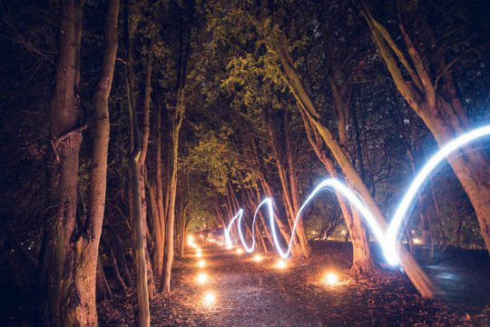 Woods at night with candles and light trail