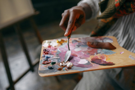 Painter holds brush and colorful paints on palette
