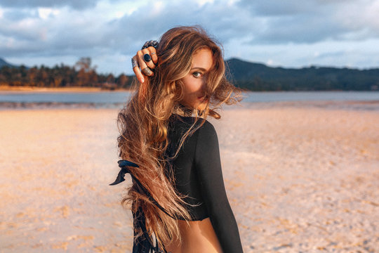 beautiful young tribal style woman on the beach at sunset