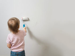 child painting the gray wall, copy space