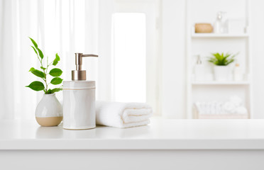 Soap dispenser and spa towel on pastel bathroom window interior
