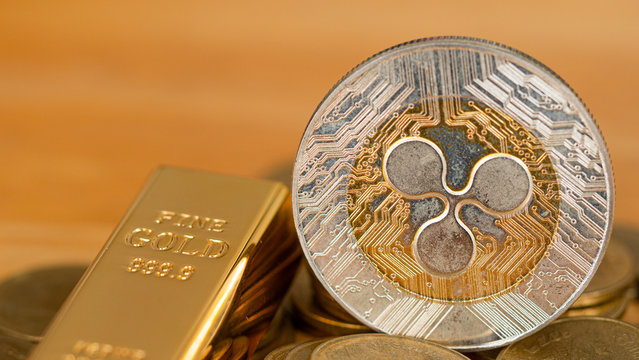 Ripple coin (XPR) and gold bar Placed on  pile of money. Concept Investors will accumulate gold or digital money.