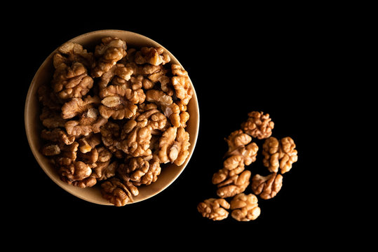 Walnut dry fruits in a brown bowl against white background