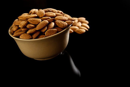 Almond Dry fruits in a brown bowl against dark background