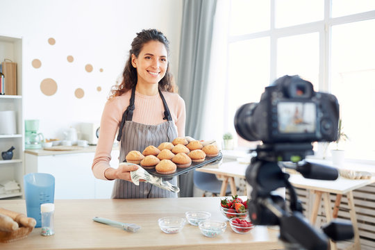 Modern young adult woman holding mold with hot cupcakes taken out of baking oven demonstrating them on camera