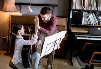 Little girl playing guitar with her music teacher in the rustic apartment