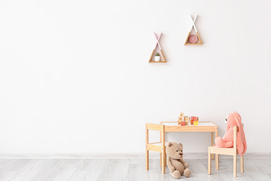Table with chairs and toys in children's room