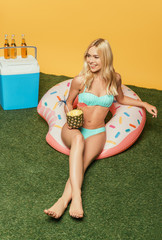 happy blonde girl sitting on swim ring with half of fresh pinapple and bottles of beer on portable fridge on yellow background
